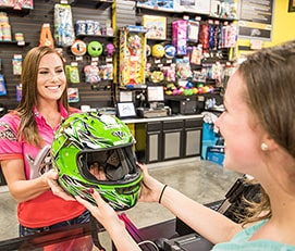 Woman giving another woman a helmet at Xtreme Racing