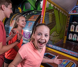 Excited girl in front of a game at the arcade in LazerPort Fun Center