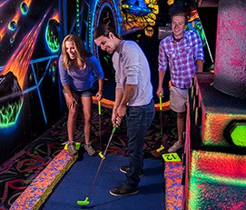 Young adults in the blacklight mini-golf course at LazerPort Fun Center