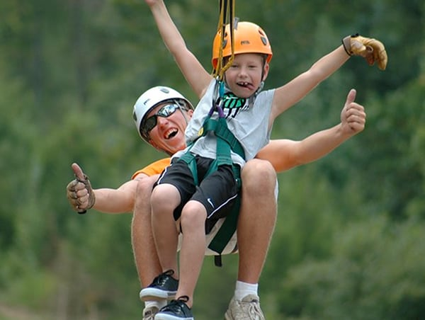 Guide and child tandem ziplining at Legacy Mountain Ziplines