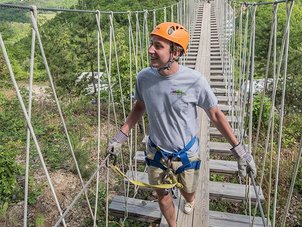 Man crossing rope bridge at Legacy Mountain Ziplines