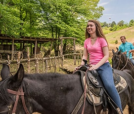 Woman horseback riding at Five Oaks Riding Stable